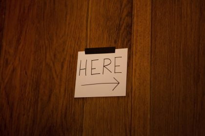 Small Handwritten sign saying 'Here' with an arrow pointing to the right.