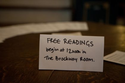 A sign on the entrance table at Conway Hall telling people that Free Readings will begin at midday in the Brockway Room
