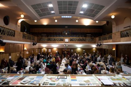 A view from the stage at Conway Hall ofa busy Small Publishers Fair, early on a winter's evening - lights in Conway Hall twinkling.