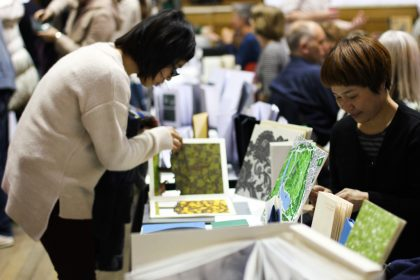A view of the fair, visitor looking closely at a publication by Chisato Tamabayashi.