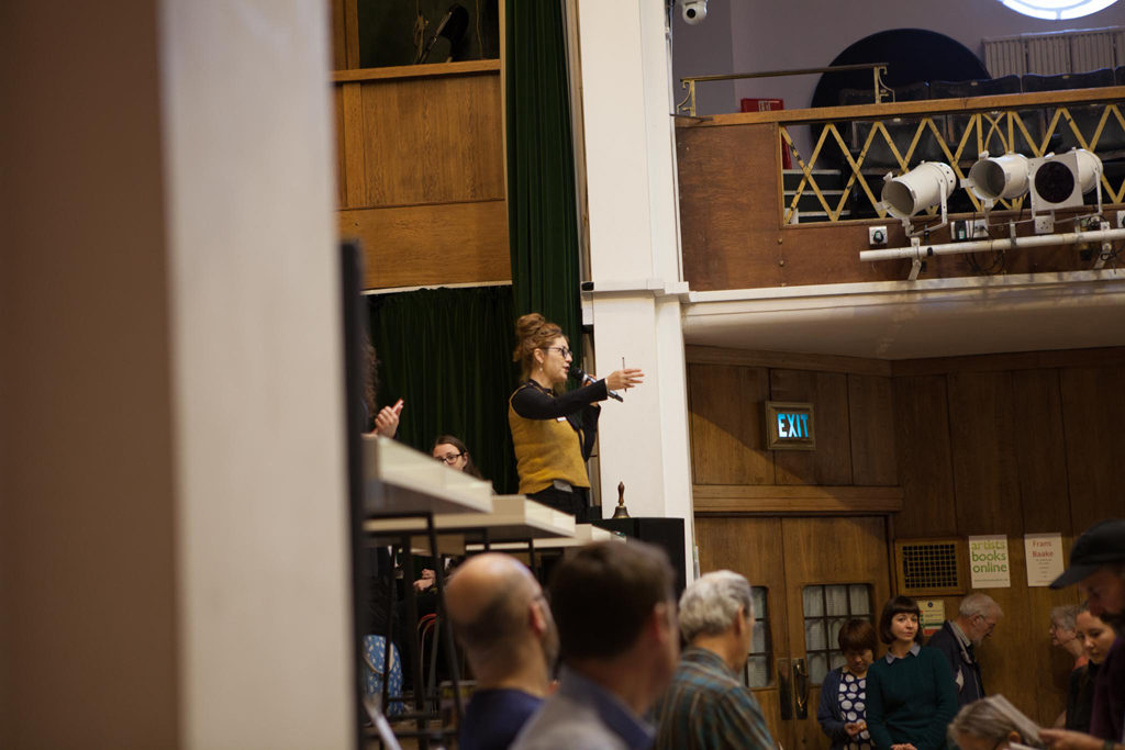 Angie Butler on stage at Conway Hall, announces the next reading. November 2018