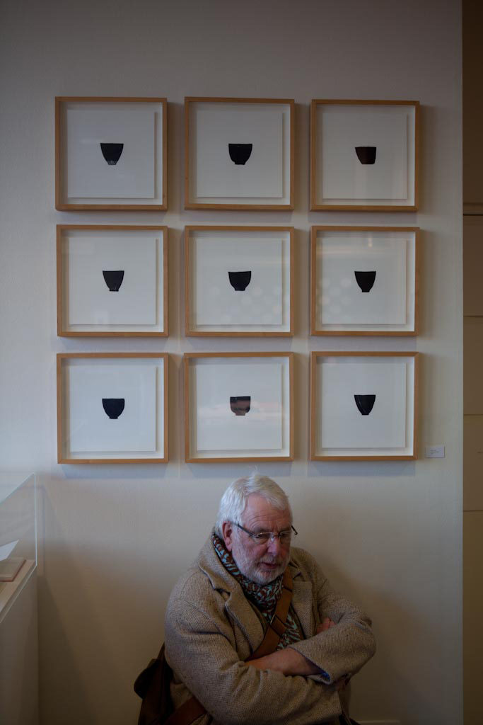 Simon Cutts in the National Poetry Library. He is seated beside 'A few cups', nine prints of cups, by Erica Van Horn